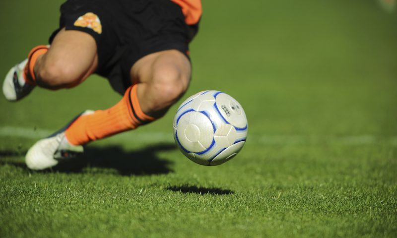 A soccer player dives for the ball on a field made of synthetic turf