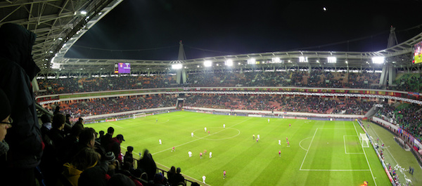 A stadium full of fans watching a soccer match being played on synthetic turf