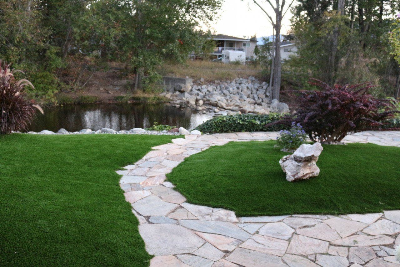 green synthetic grass in backyard of residential home how to seam artificial turf