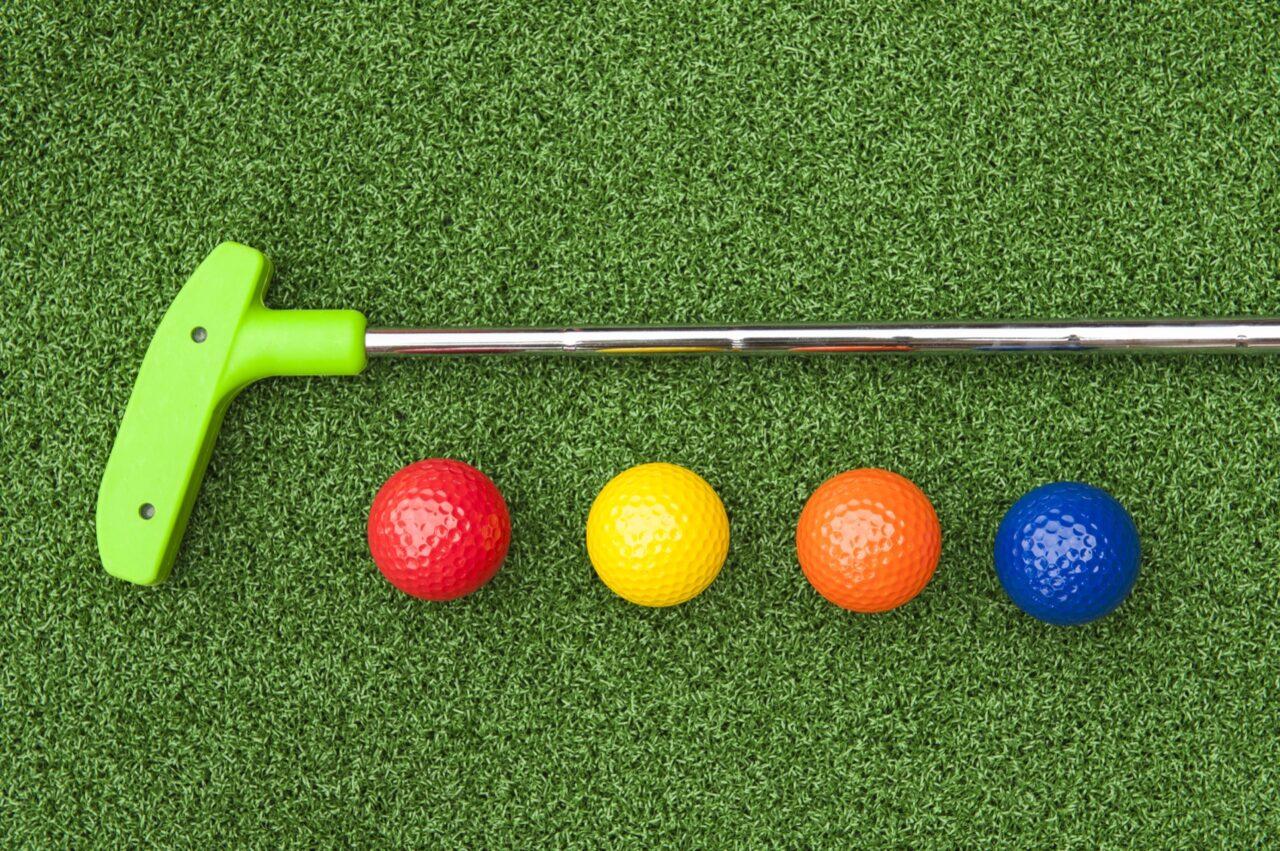 Green putter with golf balls on artificial grass