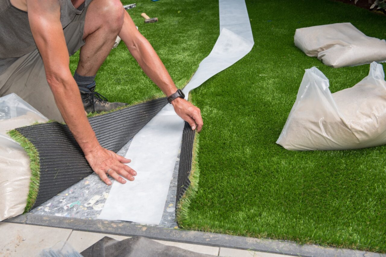 laying out artificial grass to cut
